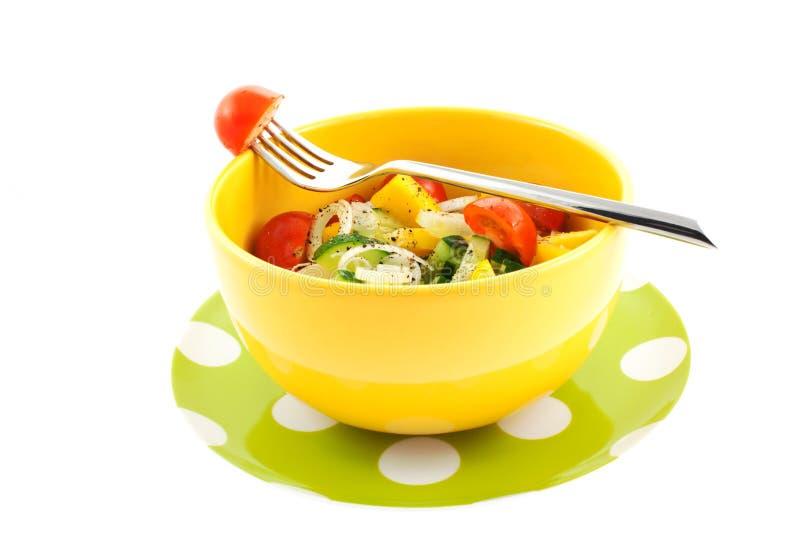 Salada vegetal em uma bacia amarela e forquilha com tomate imagens de stock