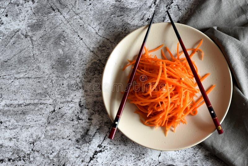 Salada vegetal picante: Cenouras coreanas em uma placa com hashis fotografia de stock royalty free