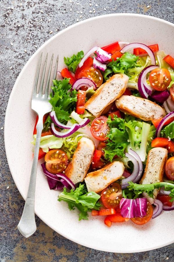 Salada vegetal saudável com peito de frango grelhado, alface fresca, tomates de cereja, a cebola vermelha e a pimenta fotos de stock
