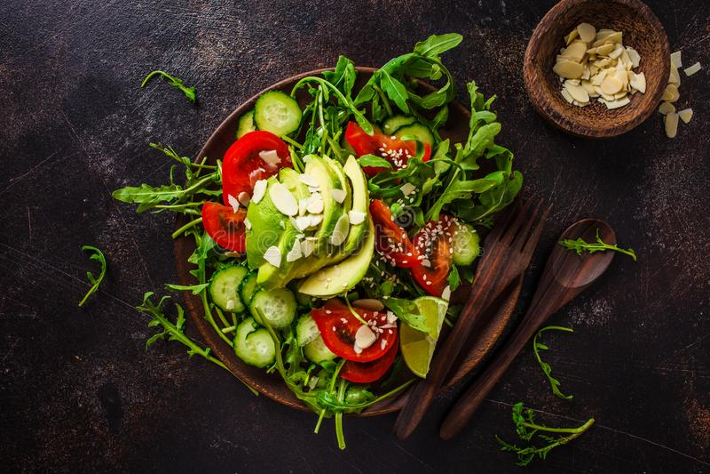 Salada verde com abacate, tomates, pepinos e porcas na placa de madeira no fundo escuro imagens de stock royalty free