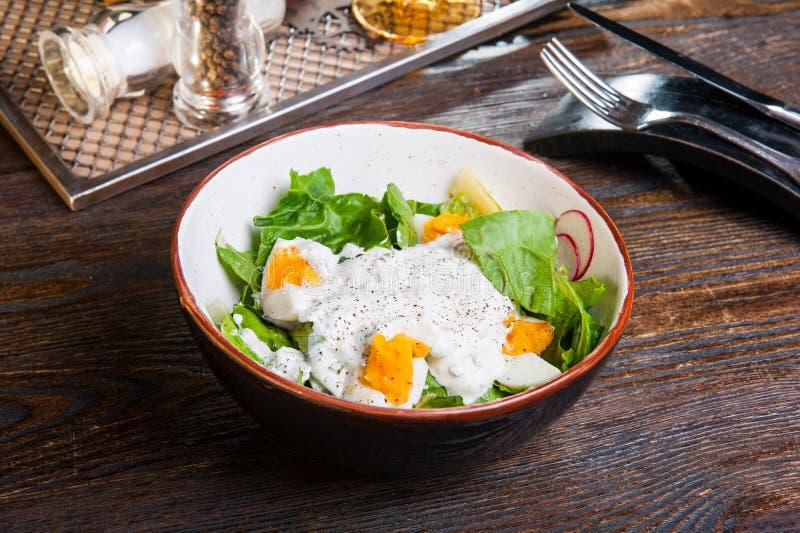 Salada verde com espinafres, iogurte e ovos cozidos na placa escura, sobre a tabela de madeira com cutlary Alimento saudável Rece imagem de stock royalty free