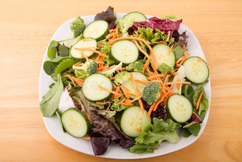 Salada verde e vegetal do campo na placa branca na tabela de madeira imagem de stock