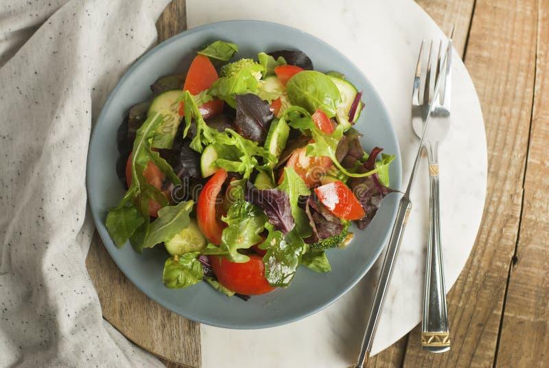 A salada verde fresca com verdes da mistura sae de espinafres, Augula, manjericão, alface, tomatoe, pepino Estilo rústico, fundo  imagem de stock royalty free