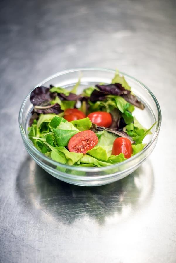Salada verde frondosa misturada pronta em uma bacia imagens de stock