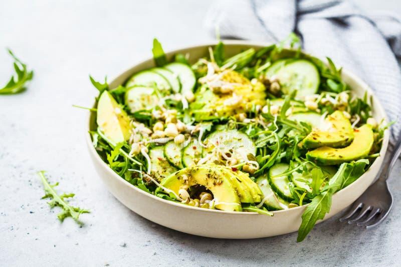 Salada verde saudável com abacate, pepino e rúcula no prato branco imagens de stock