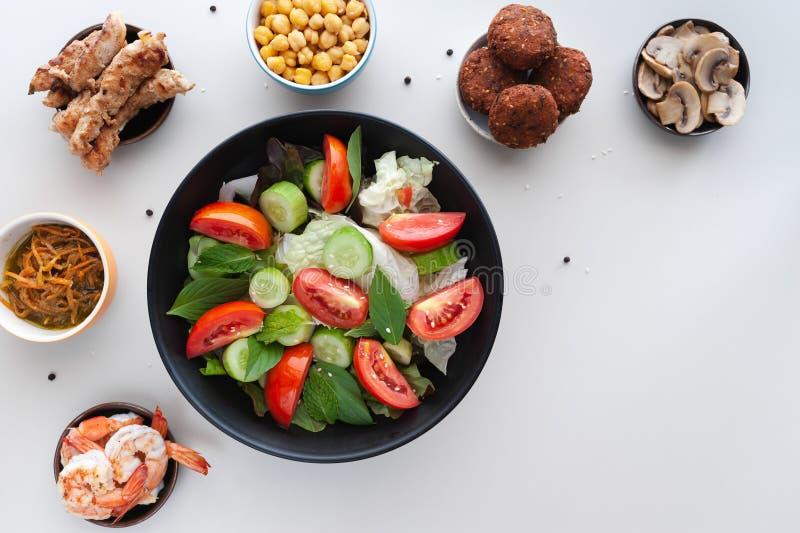 Saladas vegetais com os pratos extra na tabela branca imagem de stock royalty free