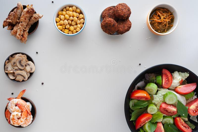 Saladas vegetais com os pratos extra na tabela branca imagem de stock