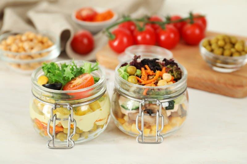 Saladas vegetais deliciosas em uns frascos de pedreiro na tabela de madeira fotos de stock