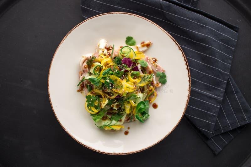 Salade épicée thaïlandaise avec le calmar et le concombre en sauce aigre-doux sur le fond noir photographie stock libre de droits