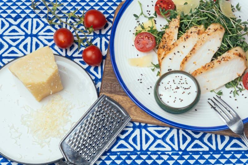 Salade avec de la salade de César de poulet avec des micro-verts, des tomates-cerises et le parmesan sur un fond bleu d'ornement image libre de droits
