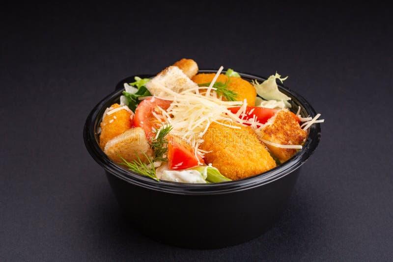 Salade avec des bandes de poulet frit sur le bacground noir images libres de droits