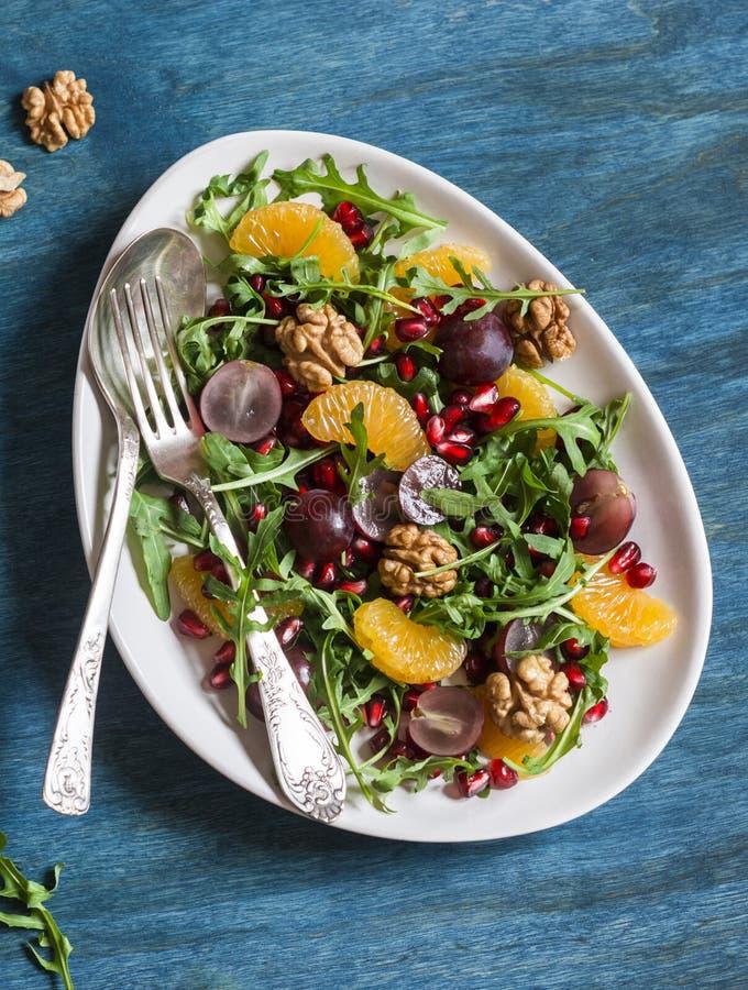 Salade avec des mandarines, des raisins, l'arugula, la grenade et des noix avec du miel s'habillant sur un fond bleu photo stock