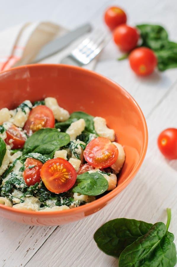 Salade avec des pâtes, des épinards, des tomates cerise et le ricotta sur le blanc images stock