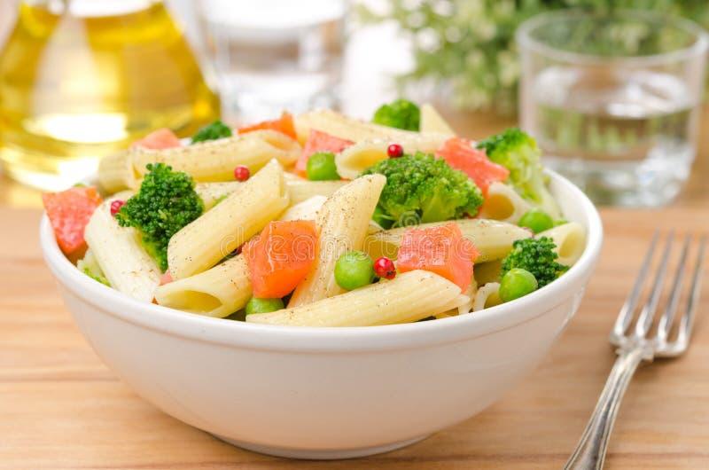 Salade avec des pâtes, des saumons fumés, le brocoli et des pois image stock