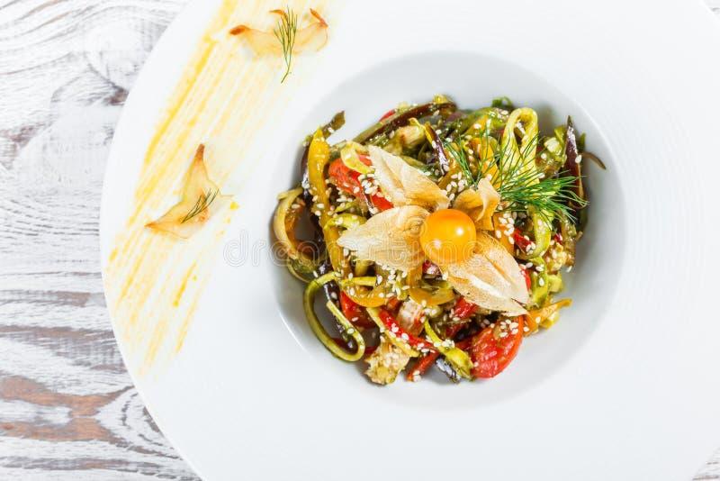 Salade avec du blanc de poulet et légumes grillés, aubergine, poivron doux, tomates, avocat et physalis de plat image stock