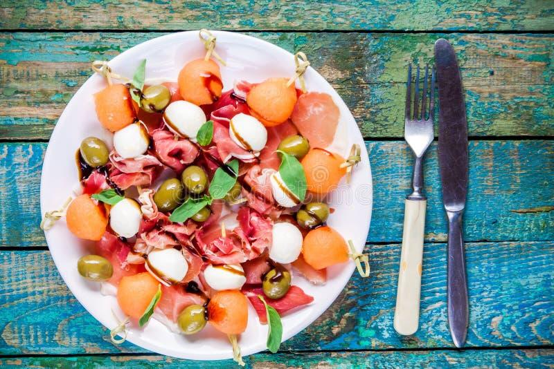 Salade avec du mozzarella, le prosciutto, le melon et les olives image libre de droits