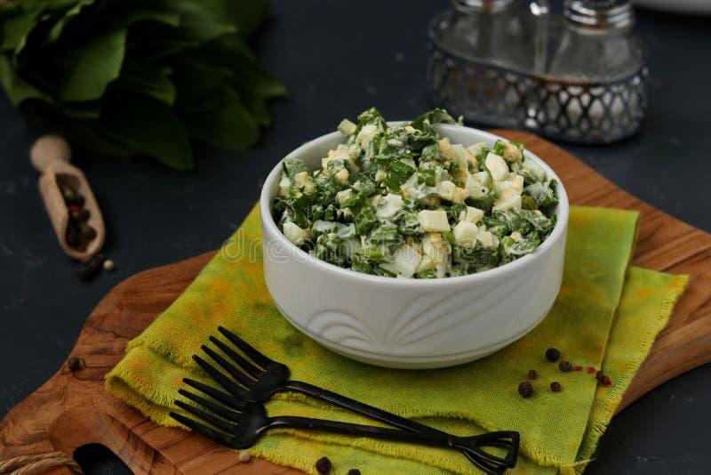 Salade avec l'ail sauvage, les oeufs et la mayonnaise de ramson dans une cuvette blanche photographie stock