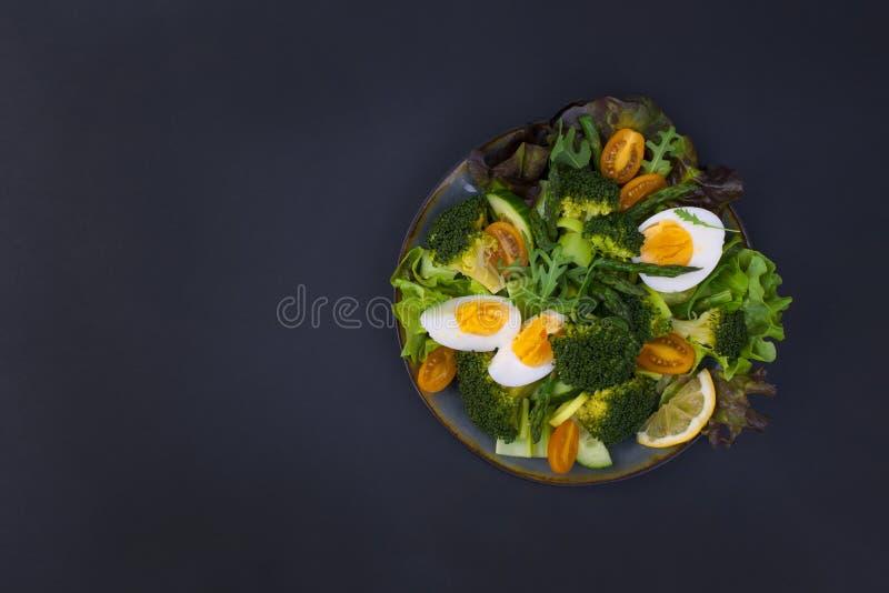 Salade avec l'asperge, brocoli, oeuf, champignons Nourriture saine verte Dîner végétarien Fond et espace noirs pour le texte plat image libre de droits
