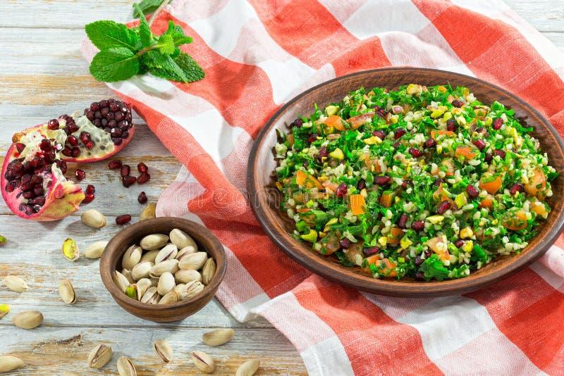 Salade avec la grenade, pistaches, persil, menthe poivrée, spr photo stock