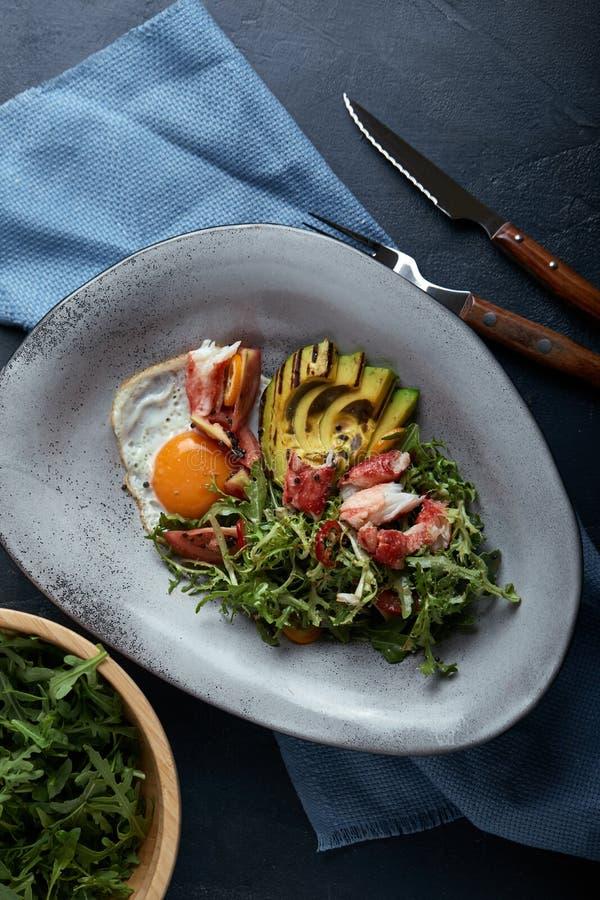 Salade avec le crabe et l'avocat sur un fond foncé La salade d'Arugula laisse assaisonné avec de la sauce sur le vin blanc avec l photos libres de droits