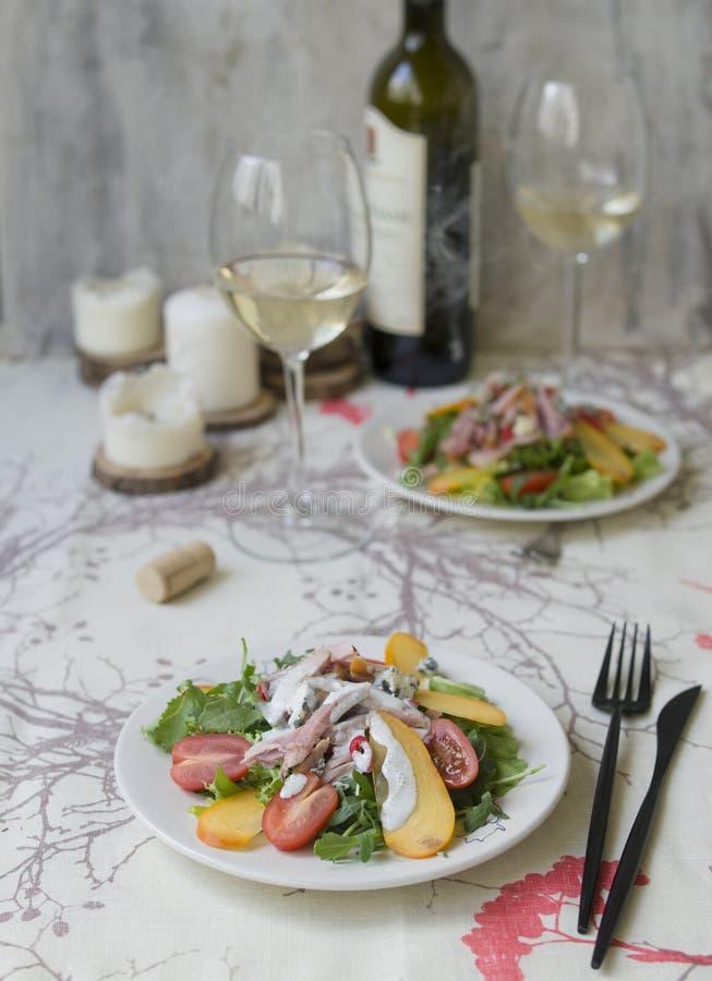 Salade avec le kaki, le poulet fumé, les tomates-cerises, le fromage de camembert et la sauce à fromage bleu Plat de fête sur un  photos libres de droits
