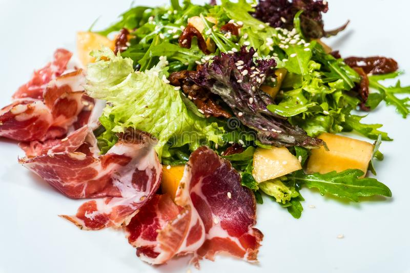 Salade avec le prosciutto et la mangue dans un plat blanc photo libre de droits