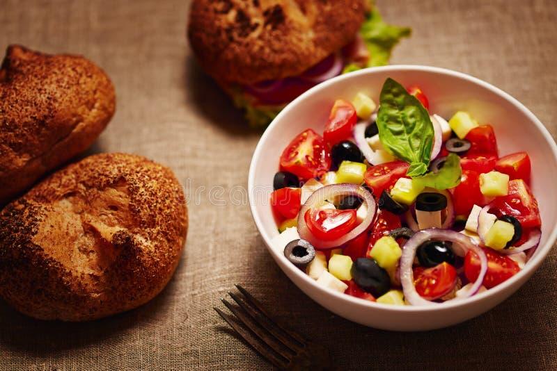 Salade avec les légumes frais et l'hamburger et les petits pains dans le dos. photographie stock