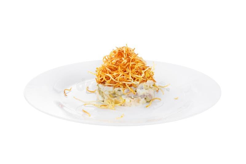 Salade avec les pommes de terre frites sur le blanc de plat d'isolement photographie stock