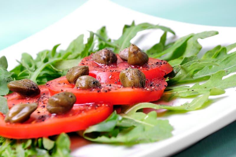 Salade avec les tomates, les câpres et l'arugul frais, a photographie stock libre de droits