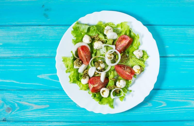 salade caprese les Cerise-tomates, les épinards de bébé et le mozzarella en métal roulent avec le pesto s'habillant sur le contex images libres de droits
