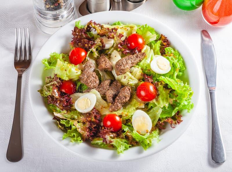 Salade chaude avec du foie, des tomates et des oeufs de poulet du plat blanc photo stock