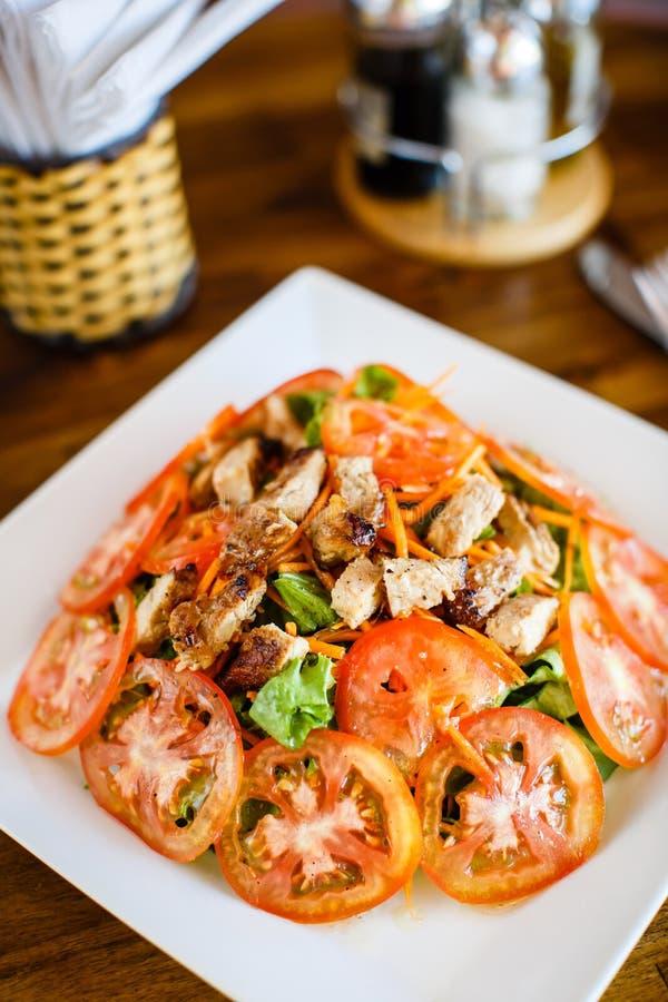 Salade chaude avec le poulet et les tomates images stock