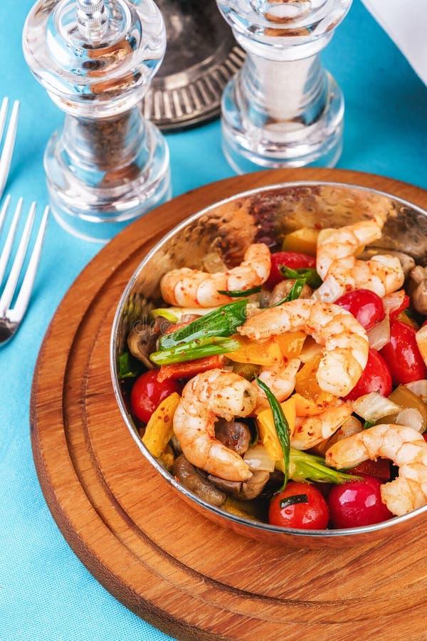 Salade chaude de poissons grillés, crevettes et moules dans une poêle à frire photos stock