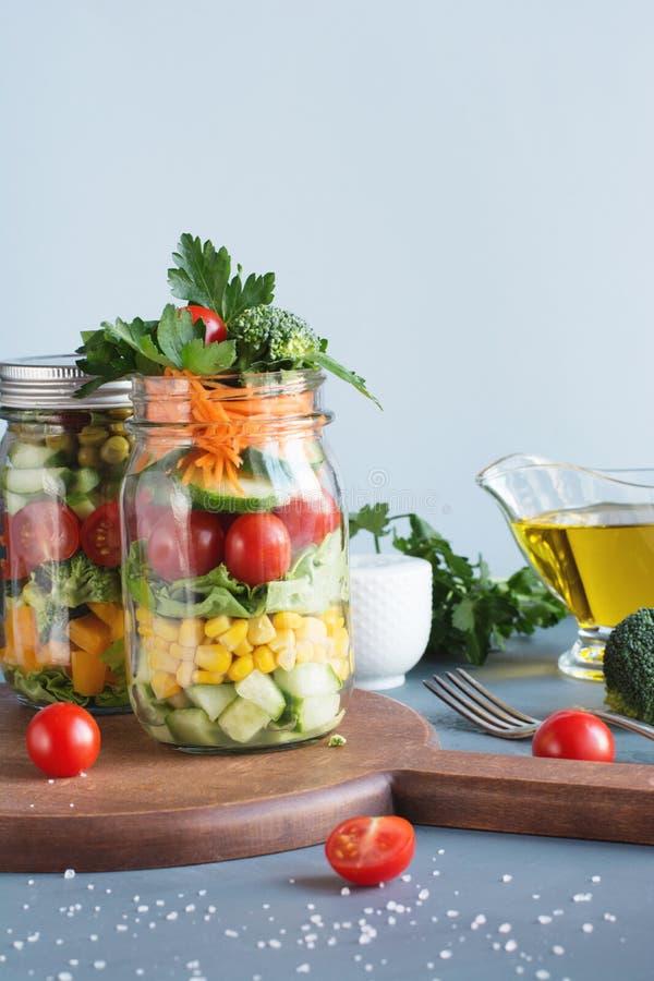 Salade colorée de detox fait maison sain végétal dans le pot de maçon avec la tomate, laitue, brocoli Copiez l'espace Déjeuner po photo libre de droits