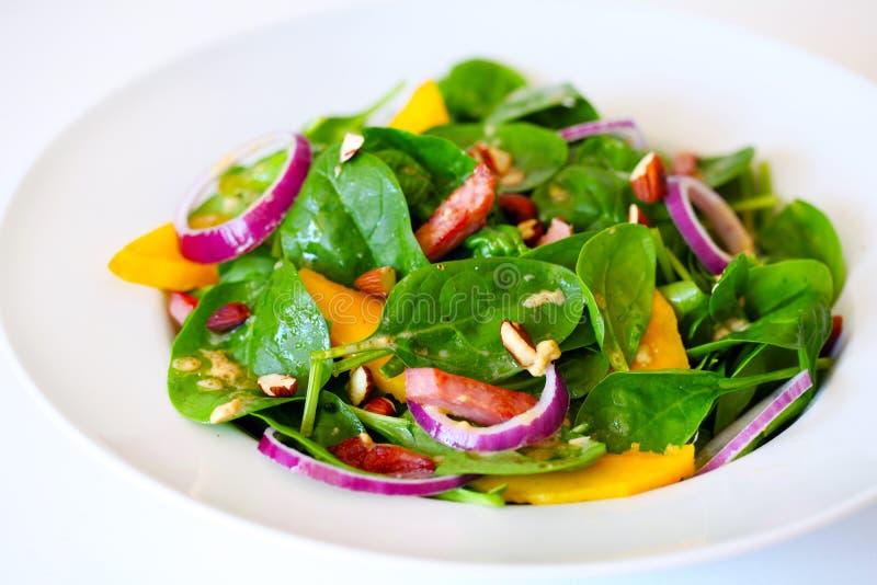 Salade d'épinards avec la mangue, le jambon, l'oignon et les amandes photos stock