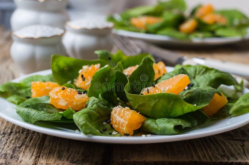 Salade d'épinards et mandarines diététiques avec le habillage et les graines de sésame de citron images stock