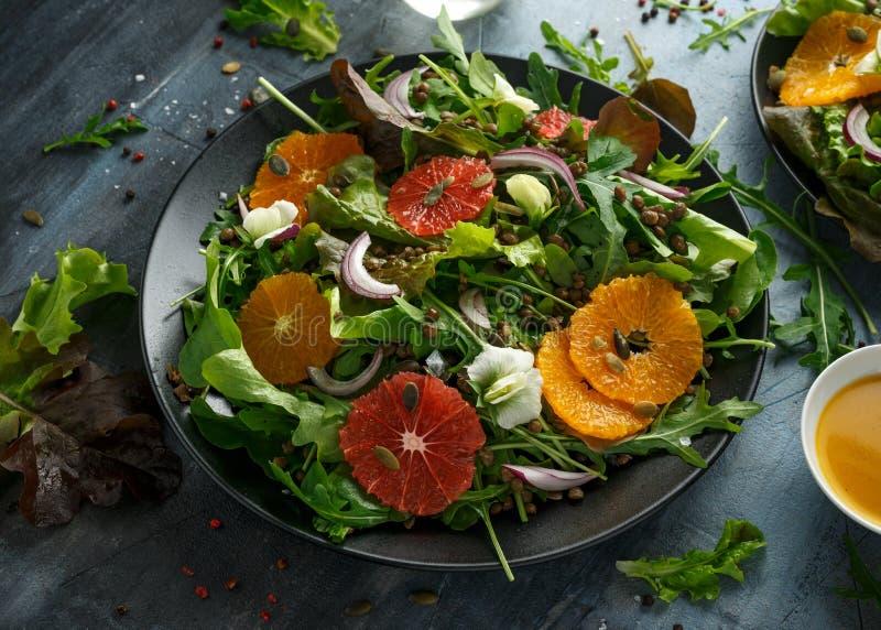Salade d'agrumes aux lentilles vertes, fusées sauvages, arugula, oignon rouge et saupoudrage de graines de citrouille photos libres de droits