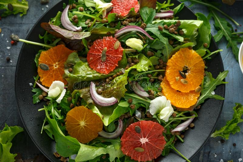 Salade d'agrumes aux lentilles vertes, fusées sauvages, arugula, oignon rouge et saupoudrage de graines de citrouille photo libre de droits