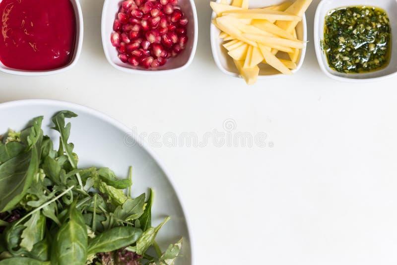 Salade d'Arugula avec les graines de grenade et la sauce, sauce à pesto et photos stock