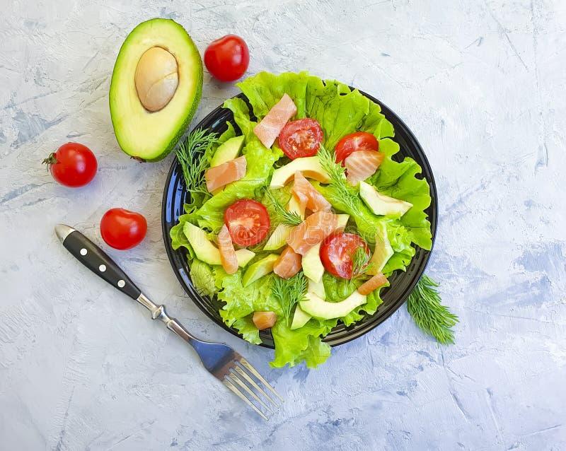 Salade d'avocat, légume rouge de poissons sur le fond concret gris photos libres de droits