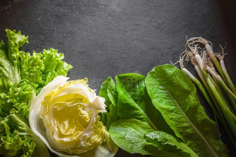 Salade d'iceberg, oignons verts et épinards sur l'ardoise grise photos stock
