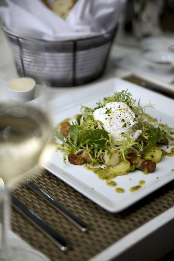 Salade d'oeufs pochés sur le frisee photos stock