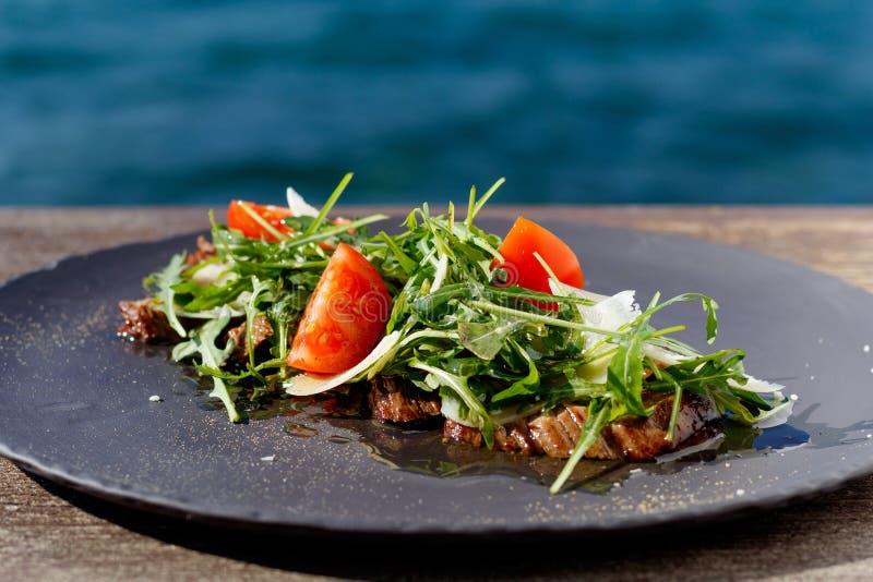 Salade de bifteck de veau avec l'arugula, laitue, moitiés de petites tomates-cerises, parmesan photographie stock libre de droits