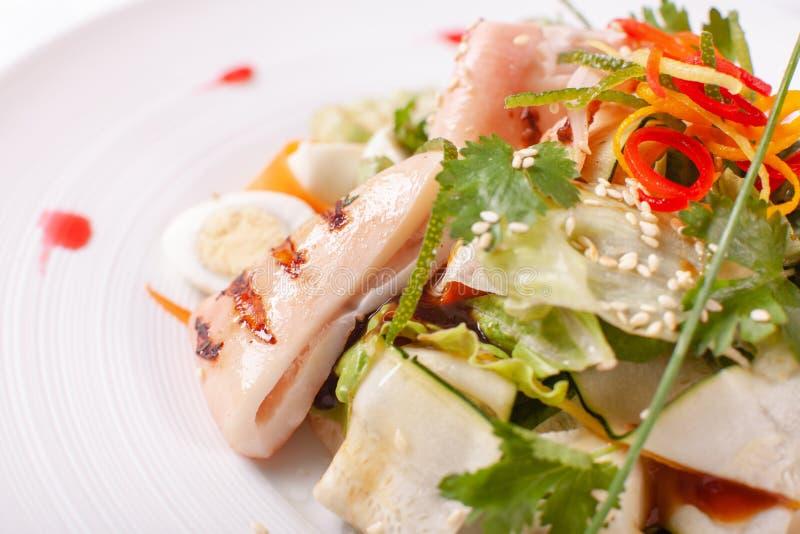 Salade de César avec des oeufs de caille, des tomates-cerises, le parmesan et le calamari grillé, poulpe dans le plat blanc sur l photos libres de droits