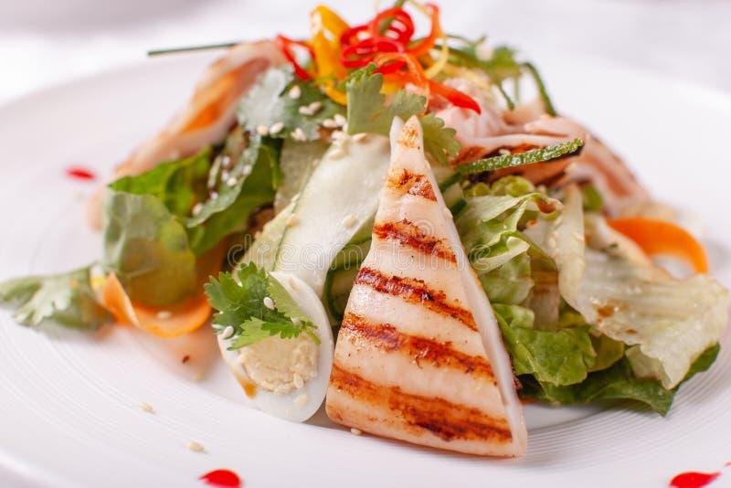 Salade de César avec des oeufs de caille, des tomates-cerises, le parmesan et le calamari grillé, poulpe dans le plat blanc sur l photographie stock libre de droits