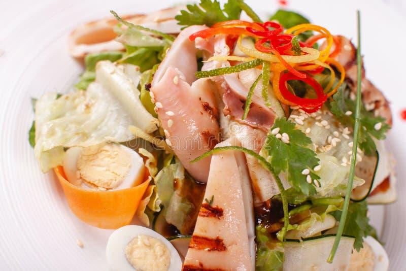Salade de César avec des oeufs de caille, des tomates-cerises, le parmesan et le calamari grillé, poulpe dans le plat blanc sur l photographie stock