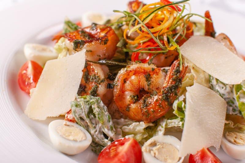 Salade de César avec des oeufs de caille, des tomates-cerises, le parmesan et des crevettes grillées dans le plat blanc sur la ta images libres de droits