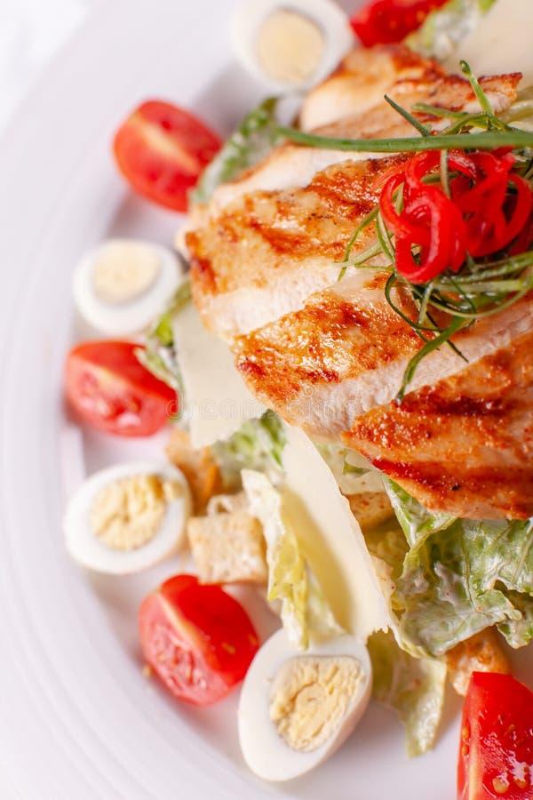Salade de César avec des oeufs de caille, des tomates-cerises, le parmesan et le poulet grillé dans le plat blanc sur la table lé photos libres de droits