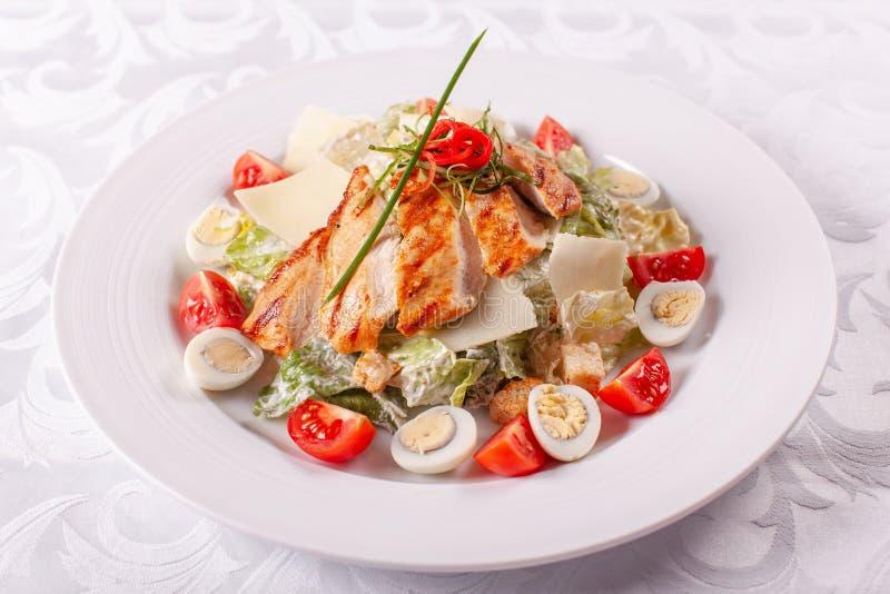 Salade de César avec des oeufs de caille, des tomates-cerises, le parmesan et le poulet grillé dans le plat blanc sur la table lé image stock
