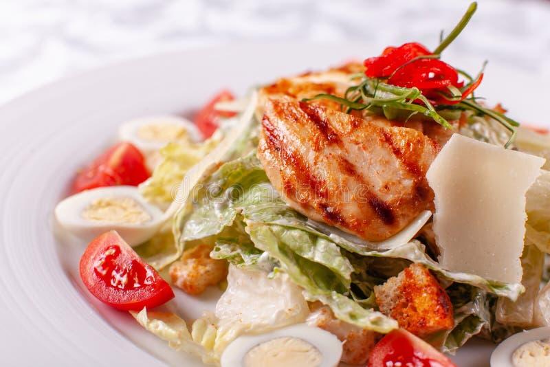 Salade de César avec des oeufs de caille, des tomates-cerises, le parmesan et le poulet grillé dans le plat blanc sur la table lé photographie stock libre de droits